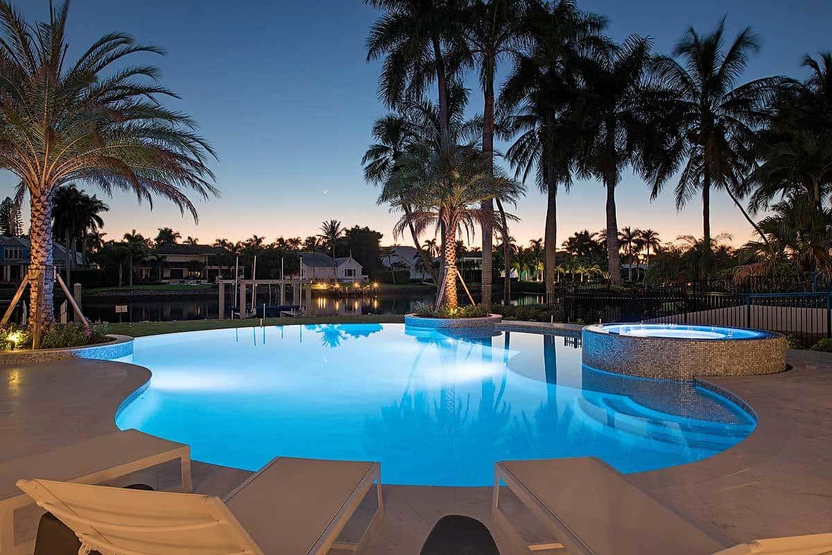 The glowing round pool is the centerpiece of this Mediterranean-style landscaping. This pool casts an almost ethereal glow to the surrounding palm trees that are planted on circular plant boxes and are adorned with spot lights that makes them glow against the twilight sky.
