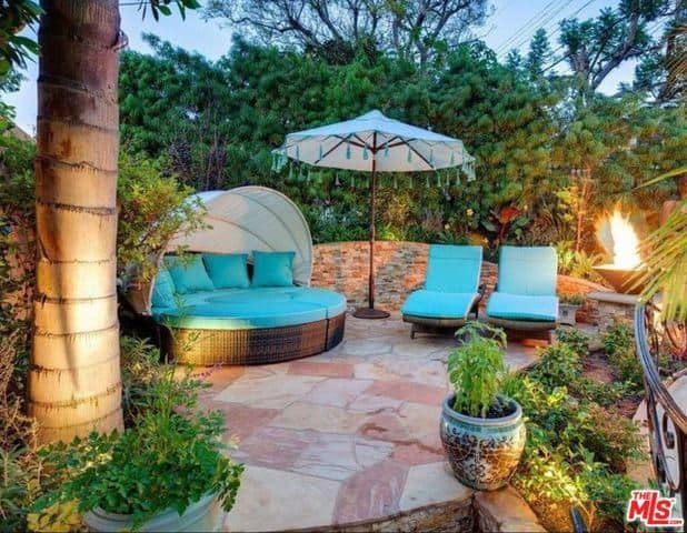 This quiet corner of the Mediterranean-style landscaping is perfect for an afternoon reading a book while relaxing on the blue cushioned day bed or on the blue cushioned lawn chairs by a firepit that casts a yellow light on the surrounding thick foliage.