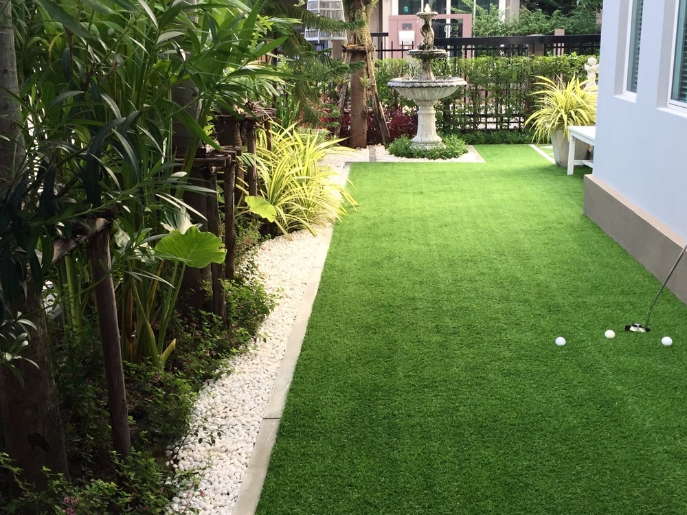 This small area beside the house is maximized with a small golf course complete with a well-manicured carpet of grass. This is bordered by white pebbles before the layer of trees and shrubberies that provide a serene background augmented by a fountain by the corner.