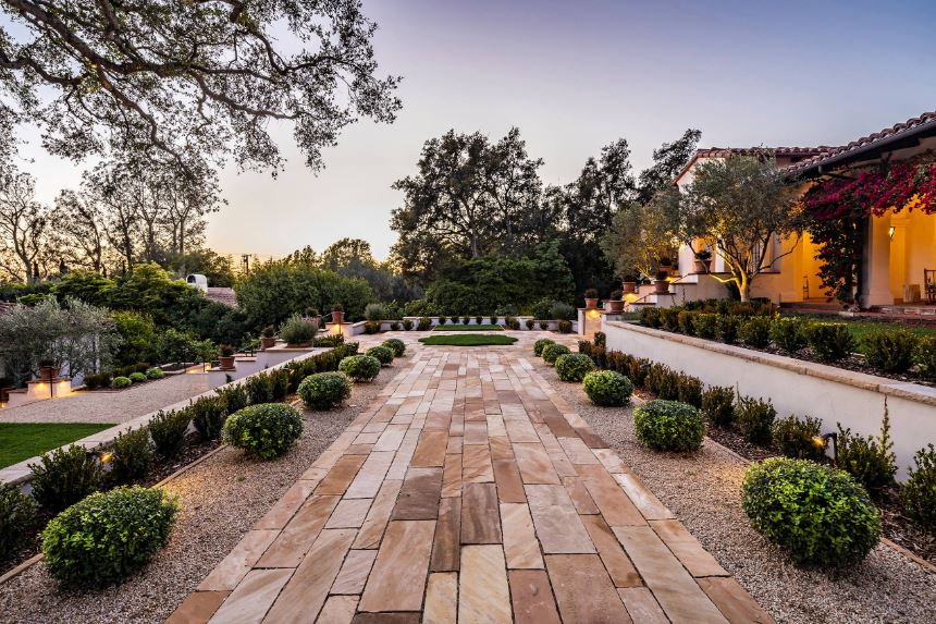 This is a neat and tidy arrangement on the Mediterranean-style landscaping that has a walkway made of terracotta bricks. This is flanked by small shrubs planted in intervals on the pebbled soil. A second layer of shrubs are added that contrasts the low white ledge.