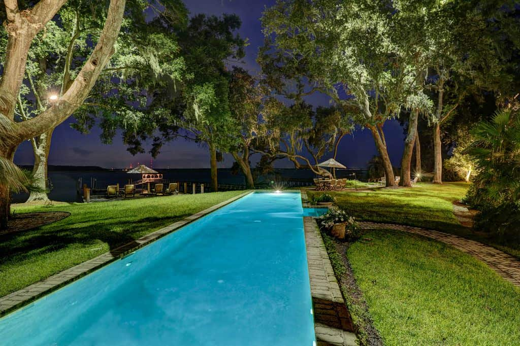 This beautiful long and narrow pool glows with an ethereal light from its light within. This serves as a nice contrast to the surrounding carpets of grass with tall trees in the distance that are light with various spot lights forming a safe circle of light against the dark night.
