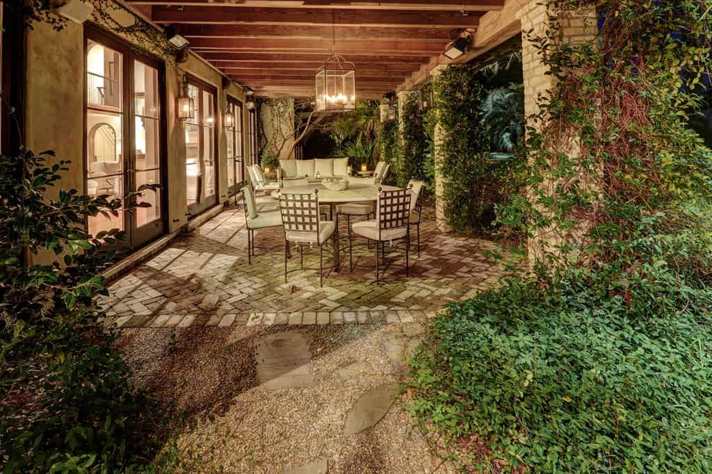 This is a charming and cozy outdoor area at the side of the home that can be accessed through glass doors flanked with lantern wall lamps. This matches with the large pendant light over the outdoor dining area adorned with stone pillars that are almost taken over by the creeping plants.