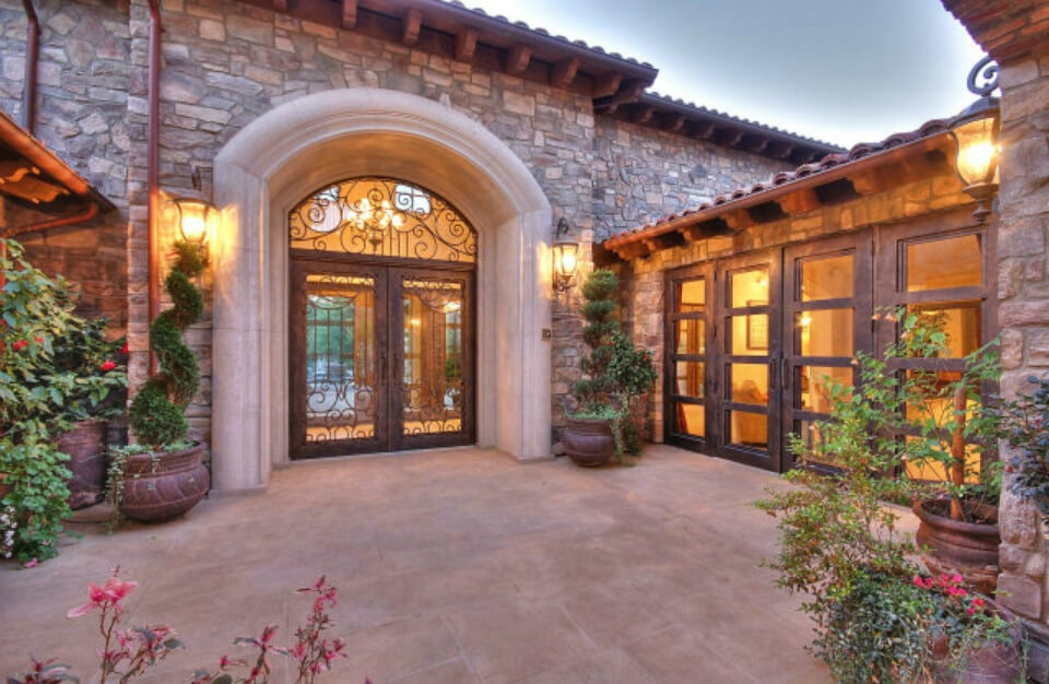 This is the arched entryway of the home that has glass doors with intricate wrought iron railings. This setup is flanked by a couple potted plants that has a shrub in it that spirals. This serves as a nice contrast to the gray stone walls with mounted lamps on it.