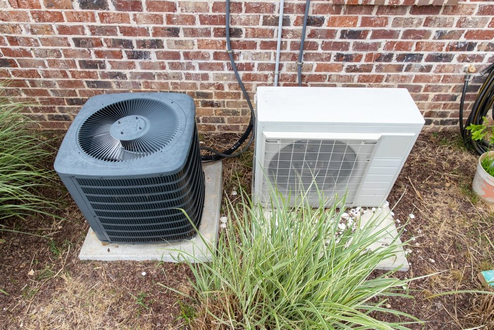 HVAC Air Conditioner Compressor and a Mini-split system side by side outside a brick home.