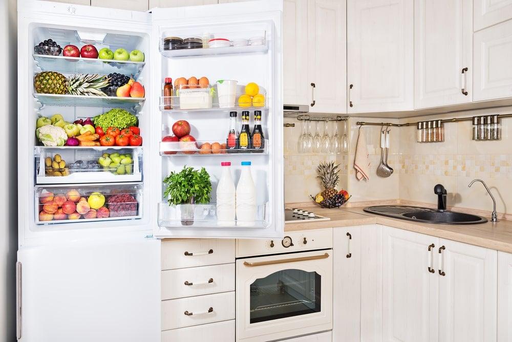 Open fridge full of fruits and vegetables.