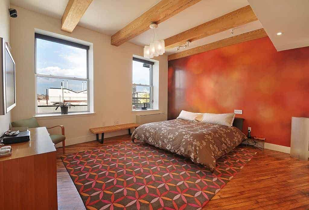 A spacious primary bedroom featuring a ceiling with beams and hardwood flooring topped by an area rug. The room has a large cozy bed and has glass windows.