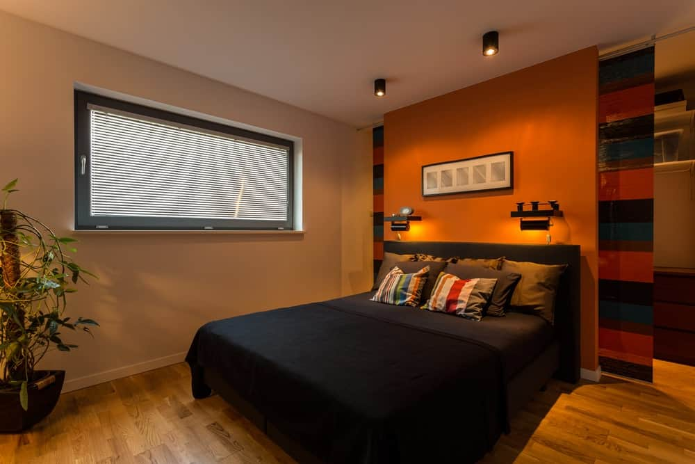 Modern primary bedroom with a modish black bed setup with an orange accent and is lighted by stylish wall lights. The room has its own bathroom as well.