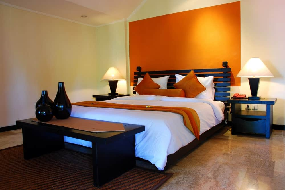 Primary bedroom with a stylish bed setup with an orange accent. The room has nice tiles flooring and white walls and ceiling.