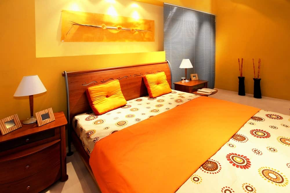 A focused shot at this primary bedroom's large and cozy bed with an orange accent. The room is surrounded by orange walls and carpeted flooring.