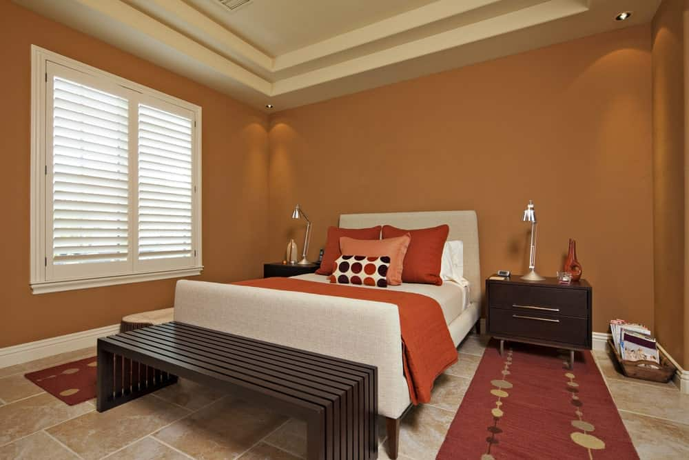 Primary bedroom with orange walls and a tray ceiling, along with tiles flooring. The room has a lovely double-sized bed with bedside tables on both sides.