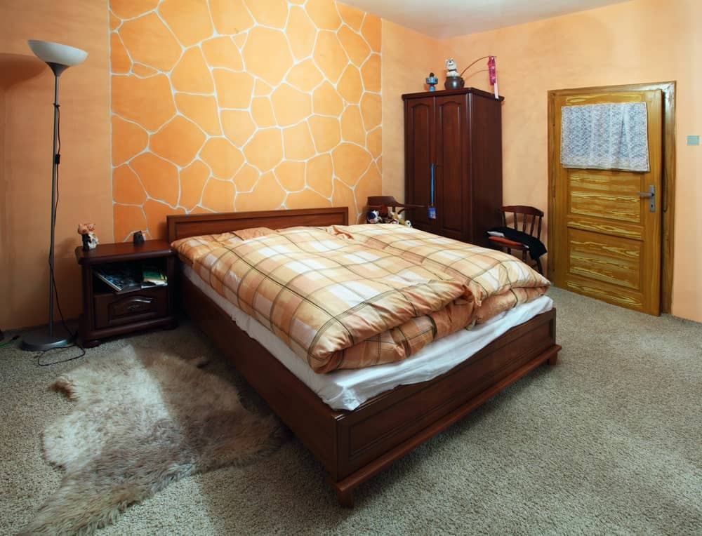 A focused shot at this primary bedroom's comfy bed with a stylish wall design at the back. The room also has gray carpet flooring.