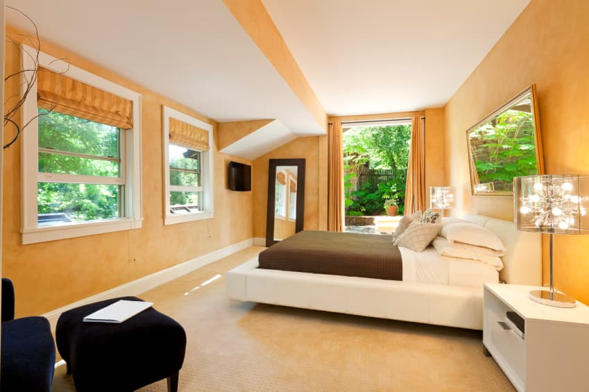 This primary bedroom offers a white bed and a modish sitting chair with a footrest on the side, surrounded by orange walls and a white ceiling.
