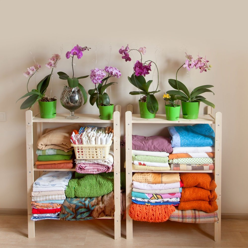 A pair of shelves with orchids and colorful folded garments.