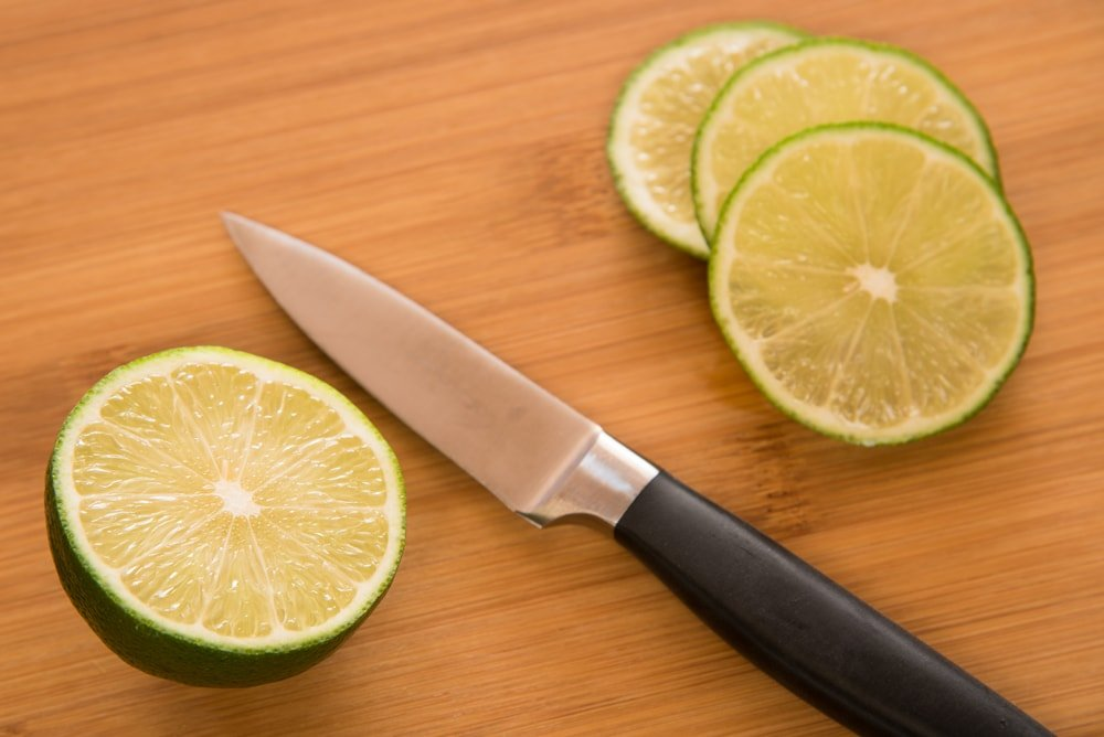A paring knife on a wooden desk beside pieces of sliced lime.