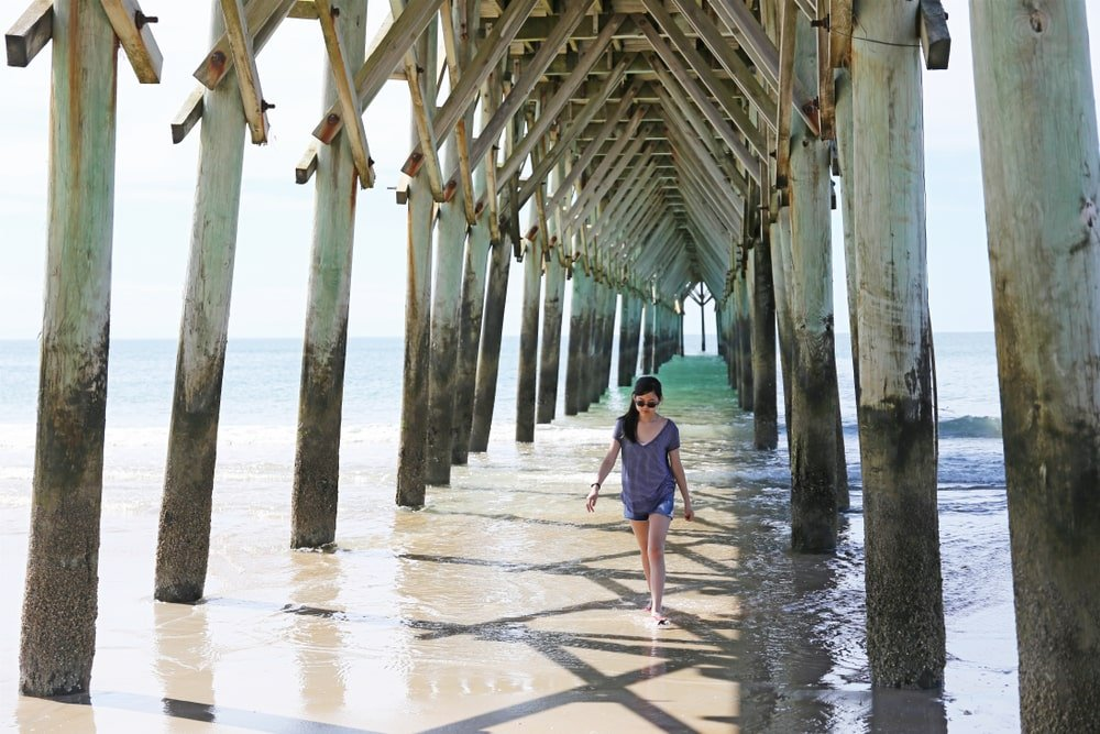 A girl walking under a pier-and-beam construction.