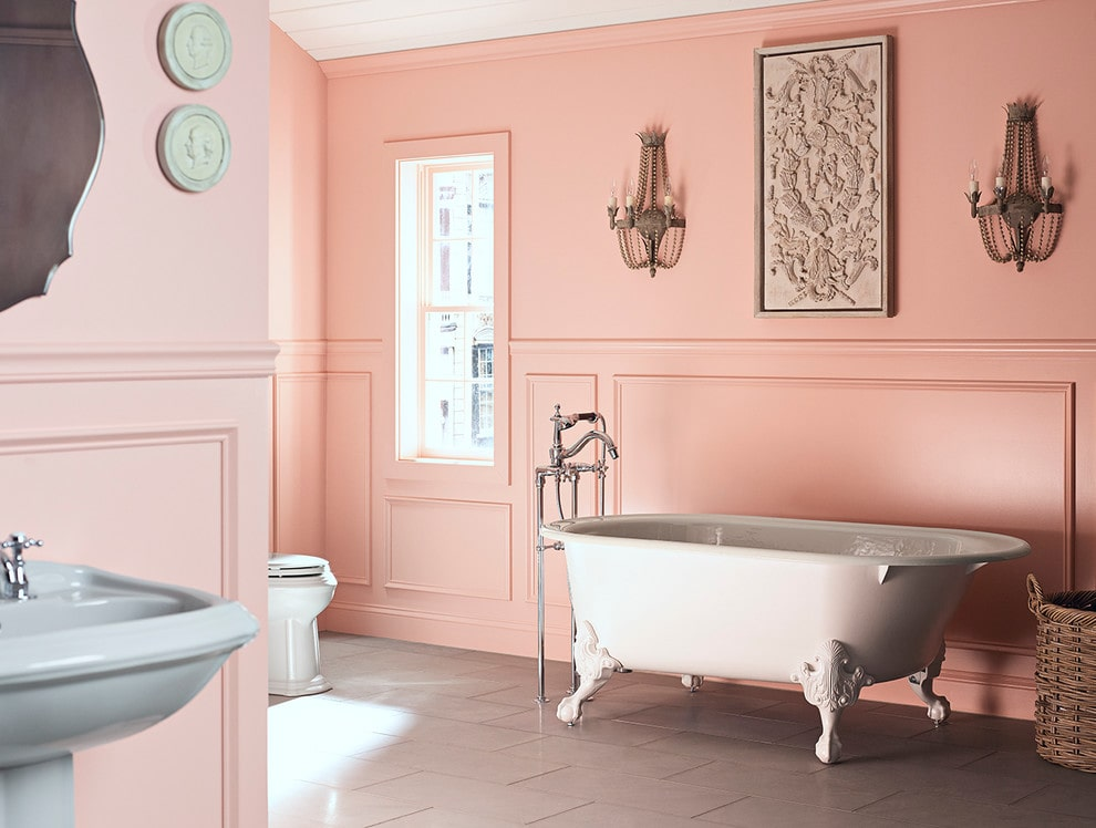 Sophisticated primary bathroom designed with wainscoting and carved wood wall arts mounted on the pink walls. It has a toilet and pedestal sink along with a clawfoot tub that's fitted with chrome fixtures.