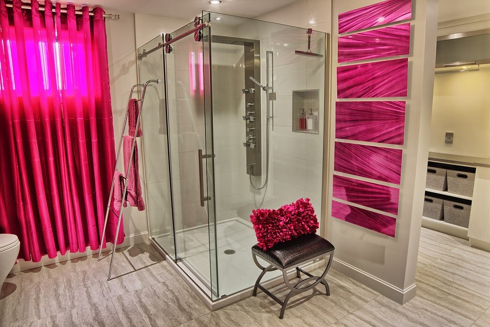 Chic primary bathroom offers a toilet and a walk-in shower enclosed in frameless glass. It is integrated with a stainless steel ladder that serves as a towel rack.