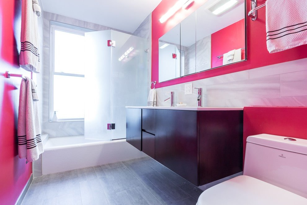 A mirrored medicine cabinet hangs above the floating sink vanity flanked by a toilet and drop-in tub that's integrated with a shower. It is illuminated by a linear sconce mounted on the pink wall.