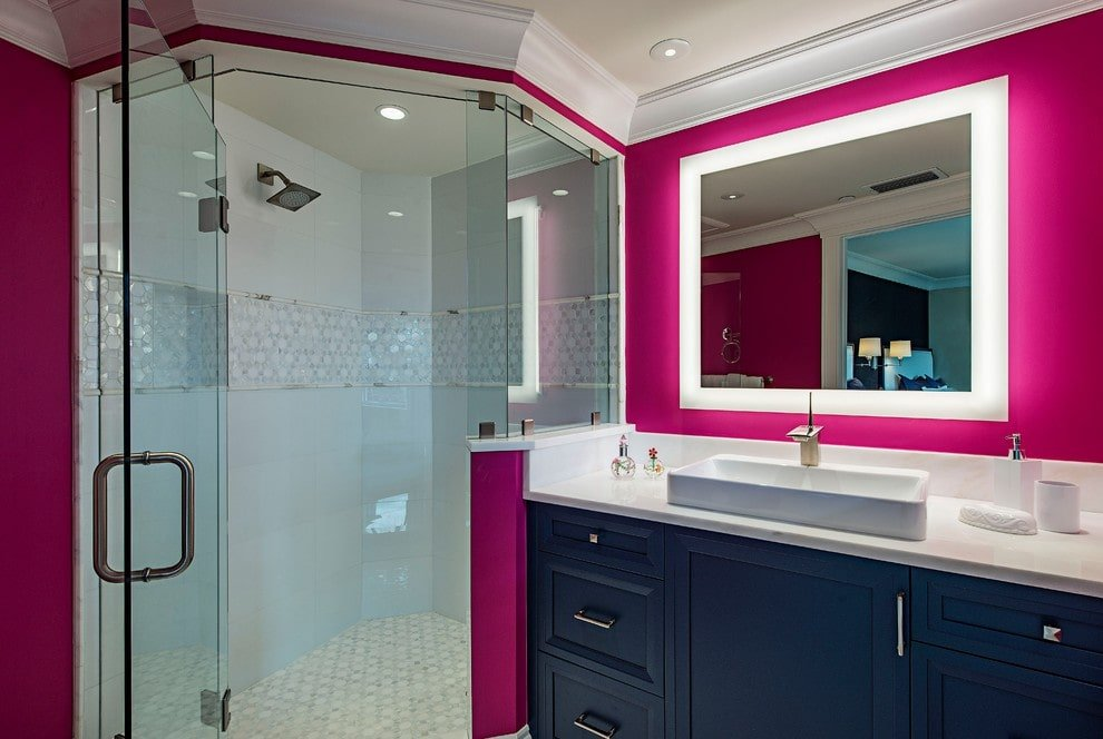A navy blue vanity topped with a vessel sink adds a striking contrast to the magenta walls mounted with a luminous mirror. It is accompanied by a walk-in shower that's enclosed in frameless glass panels.