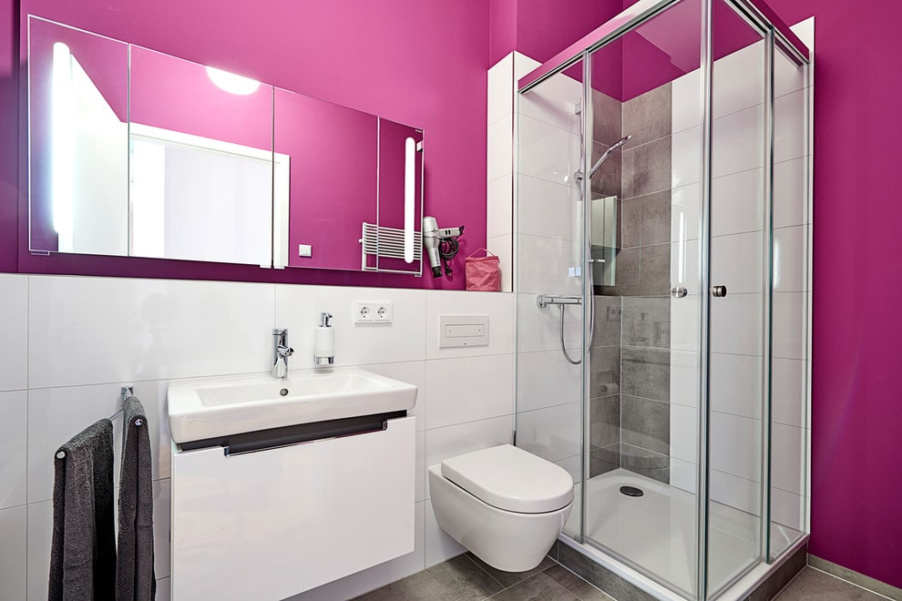Contemporary primary bathroom with a mirrored medicine cabinet and a modern toilet flank by floating sink vanity and walk-in shower. It has gray tiled flooring and pink walls fitted with white backsplash.