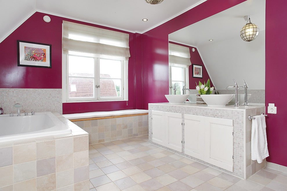This primary bathroom is decorated with a spherical pendant and a black framed artwork mounted on the pink wall. It has dual vessel sink vanity and a deep soaking tub by the glazed window covered in translucent roman shade.