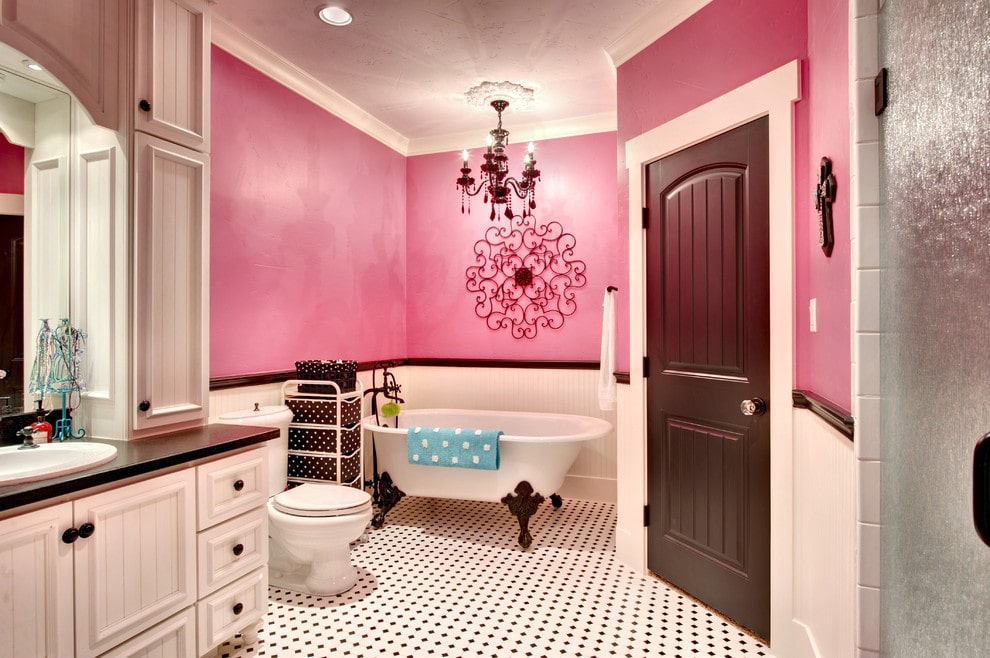 An ornate wrought iron wall art stands out against the pink walls in this primary bathroom with a beadboard vanity and a toilet over white tiled flooring accented with black diamond pattern. It includes a clawfoot tub lighted by a candle chandelier.