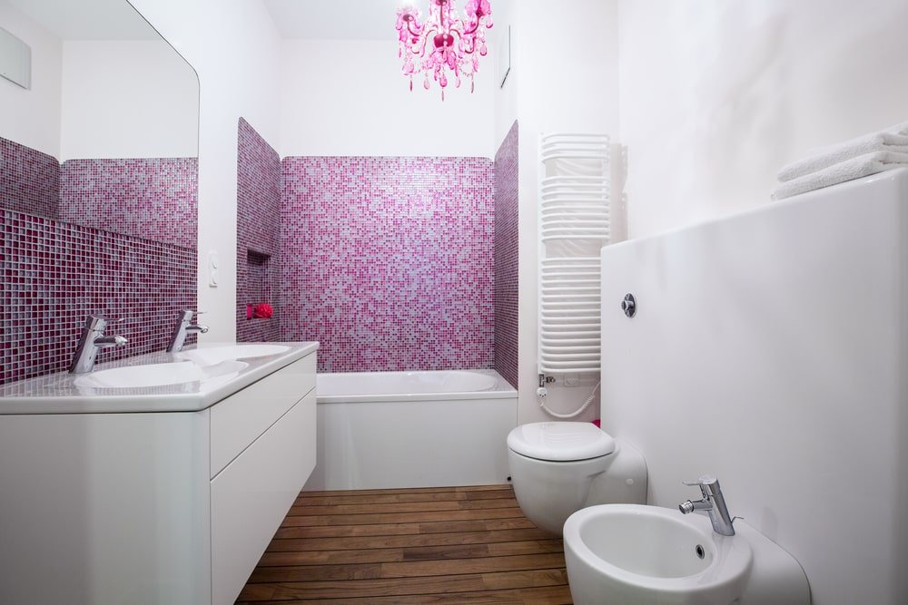 Contemporary primary bathroom with modern toilets and a sleek vanity paired with a frameless mirror. It includes a gorgeous pink chandelier and stunning mosaic tile backsplashes that bring a pop of color in the room.