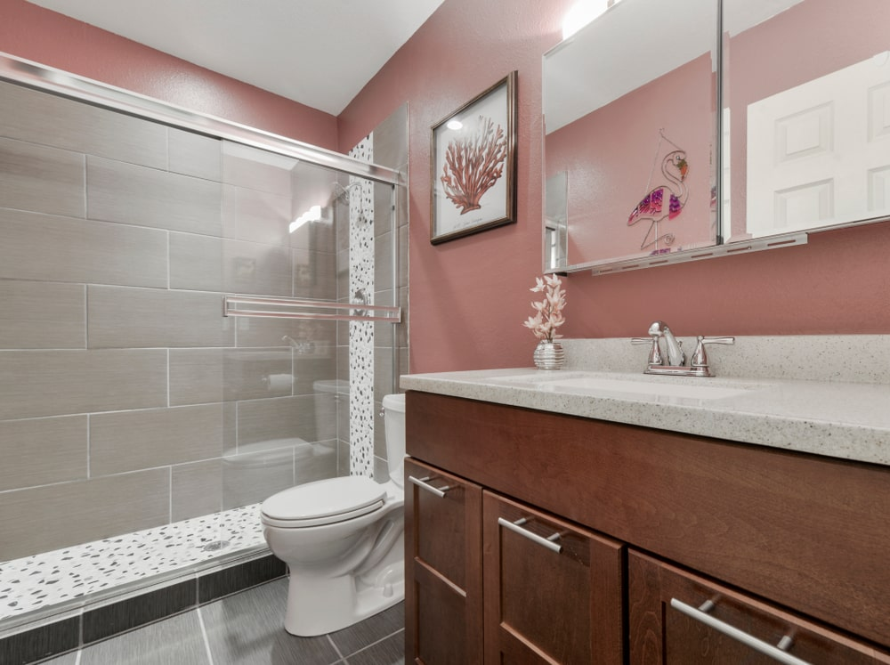This primary bathroom features a walk-in shower and a toilet next to the natural wood vanity that's topped with a granite countertop. It has gray tiled flooring and pink walls mounted with a mirrored medicine cabinet and a lovely artwork.