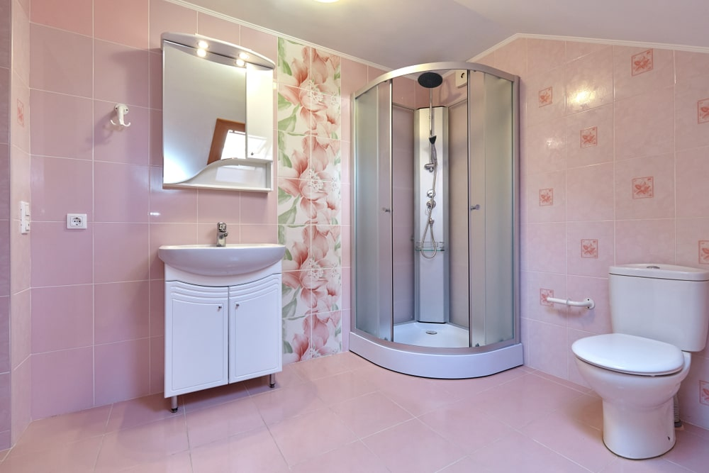 Decorative floral tiles add a nice accent in this primary bathroom boasting a toilet and a walk-in shower along with vessel sink vanity that's paired with a stylish medicine cabinet.