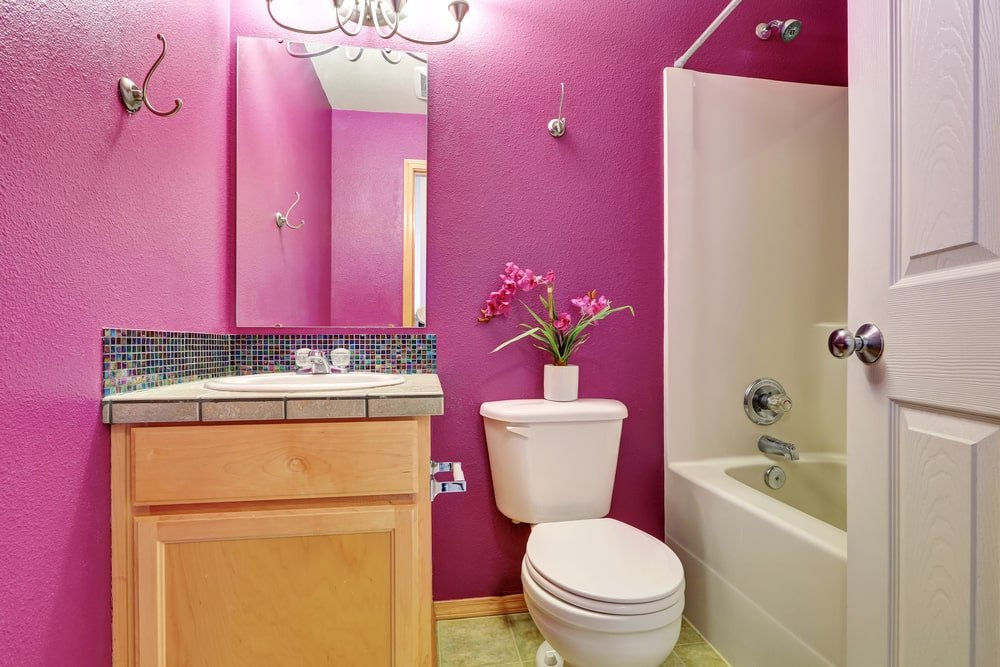 Wooden sink vanity along with a tub and shower combo flank a toilet that's topped with a lovely flower vase. It is illuminated by a chrome sconce mounted on the pink wall.