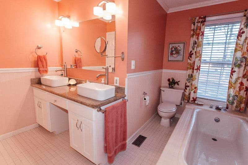 The pink primary bathroom features his and her vessel sinks sitting on a granite top vanity. There's a drop-in bathtub on the side accompanied by a toilet and a louvered window dressed in floral curtains.