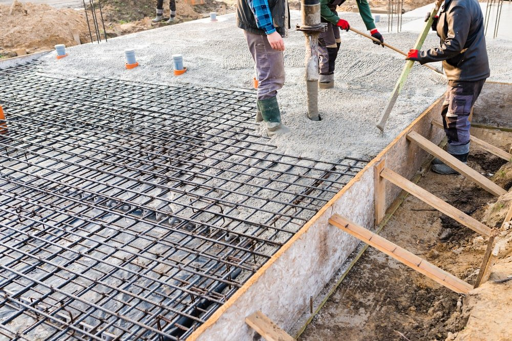 Three workers pouring concrete on the house foundation.