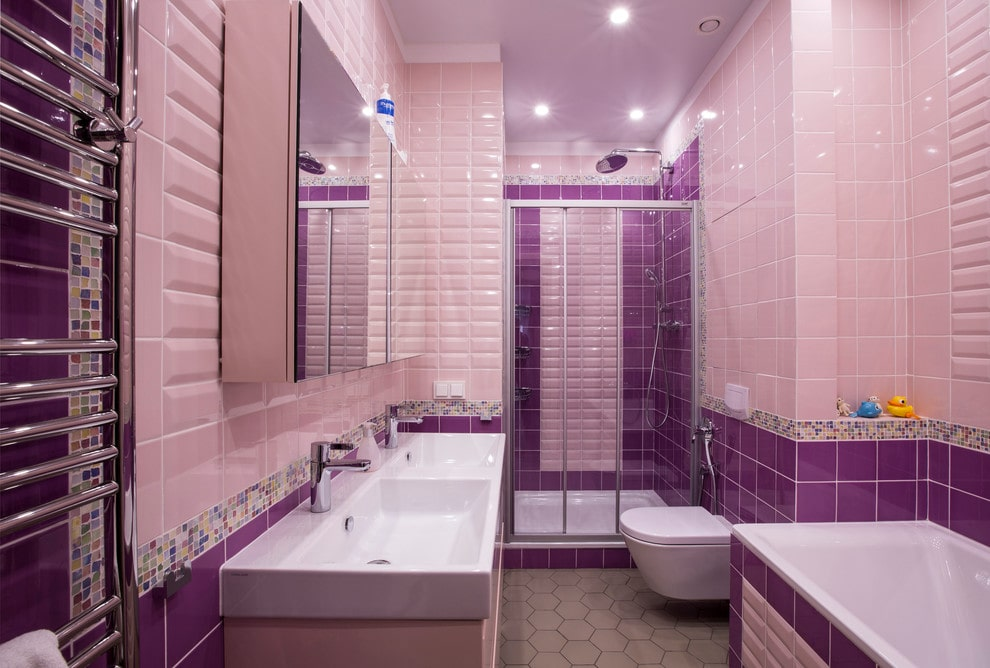 A medicine cabinet with mirrored doors hangs above the dual sink vanity that's fixed against the purple tiled wall. It is accompanied by a deep soaking tub and a modern toilet sitting next to the walk-in shower.