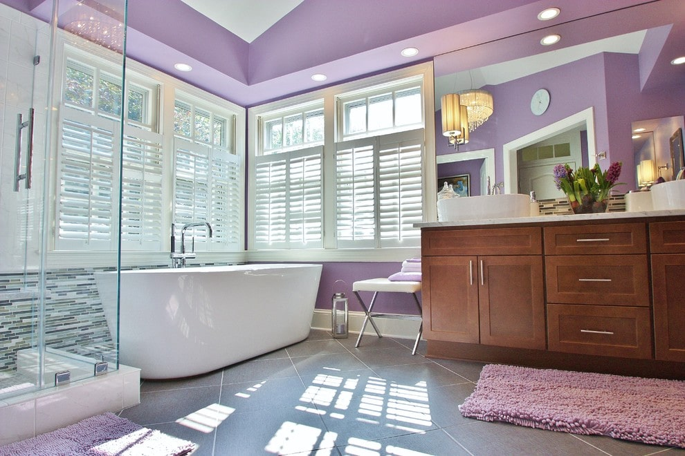 Natural light streams in through the louvered windows in this master bathroom showcasing a freestanding tub and a wooden vanity with vessel sinks and a sleek seat on the side. It has a vaulted ceiling and concrete tiled flooring topped by purple rugs.