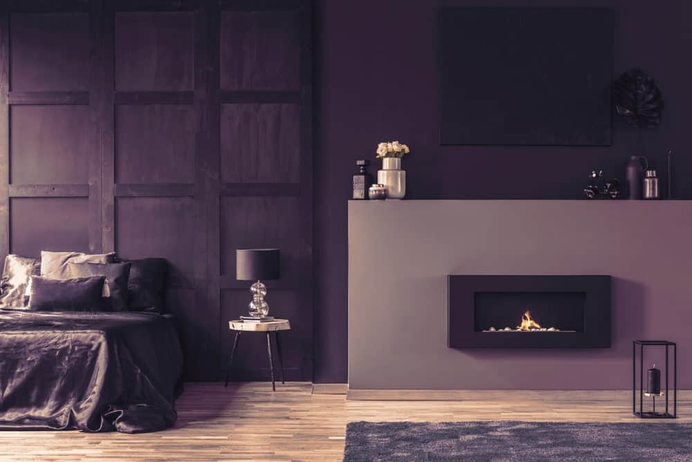 A look at this primary bedroom's stunning purple walls along with a purple bed setup. The room also offers a large modern fireplace.