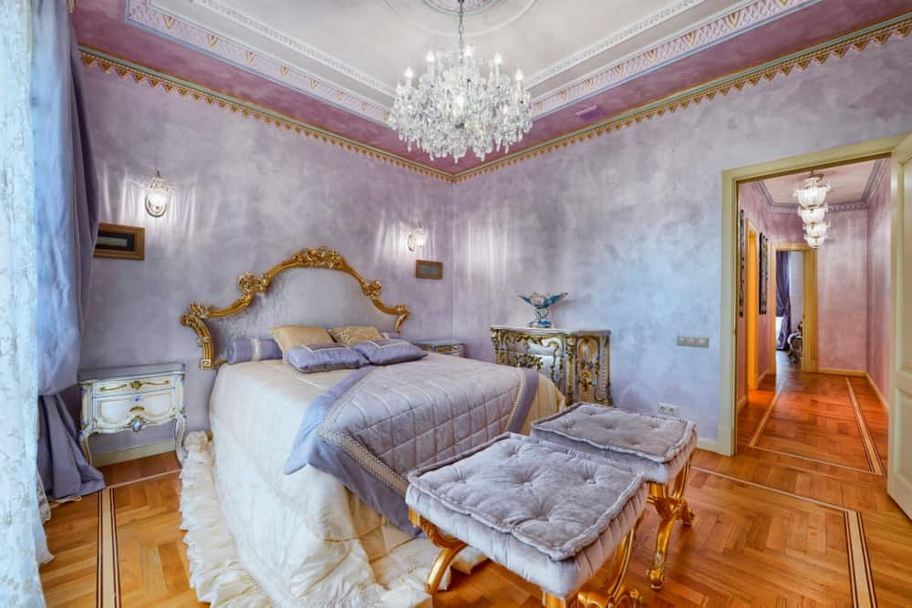 This primary bedroom offers an elegant bed setup surrounded by beautiful purple walls. The room features decorated hardwood floors and a gorgeous tray ceiling lighted by a glamorous chandelier.