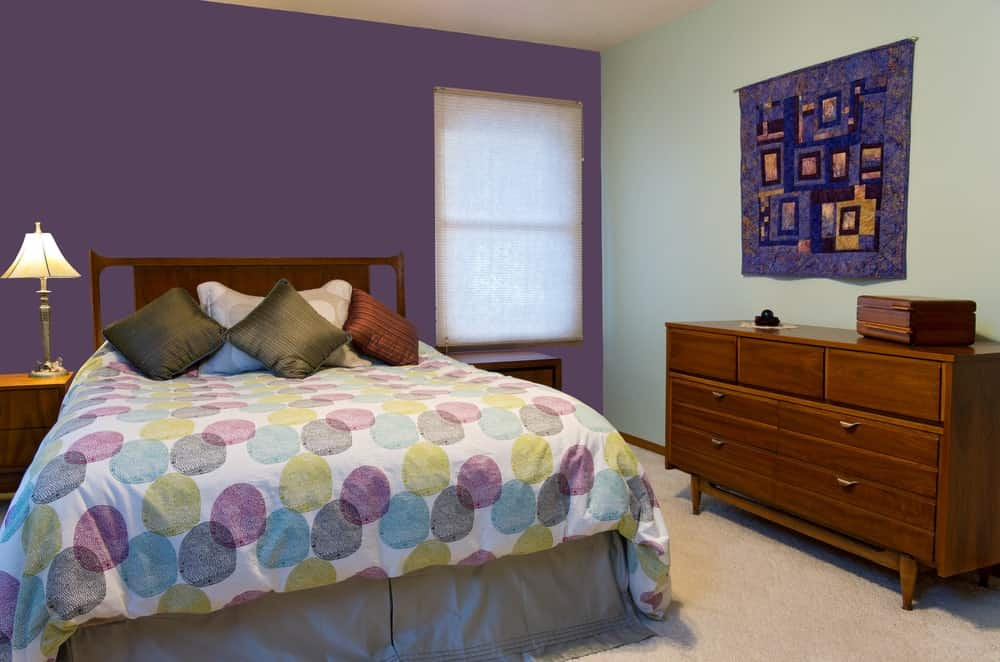 This bedroom offers a nice bed setup lighted by a table lamp on the side. The room has a purple wall and carpet flooring.