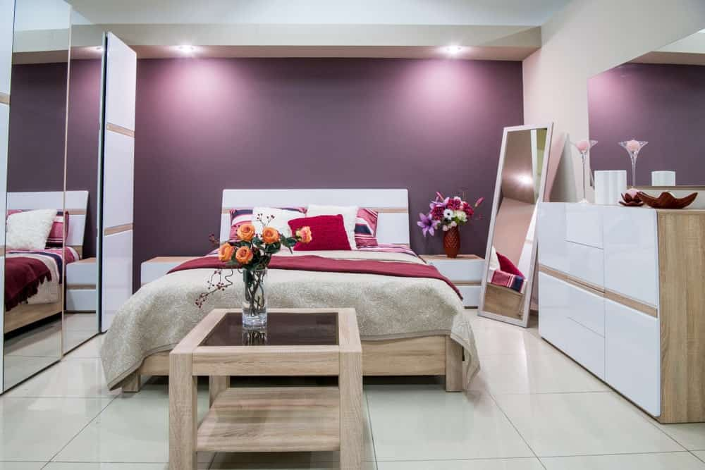 A focused shot at this bedroom's large bed set lighted by recessed ceiling lights. The room has medium-tiles flooring and a white ceiling, along with a purple wall.