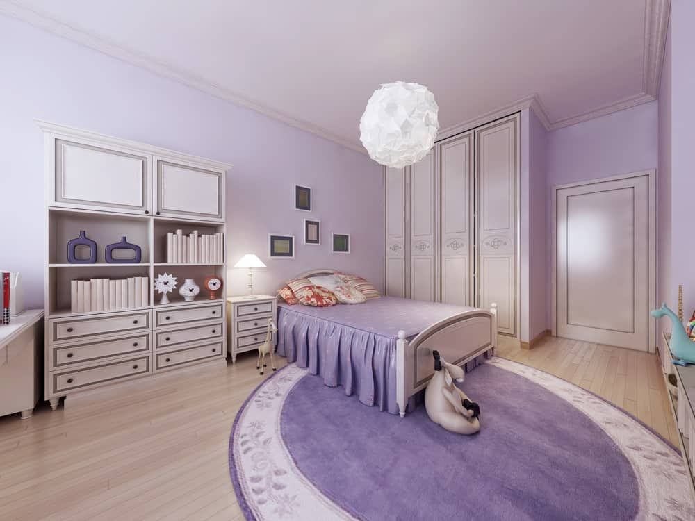A spacious primary bedroom featuring a gorgeous purple bed along with a large round area rug. The room is surrounded by purple walls. The room is lighted by a charming ceiling light.