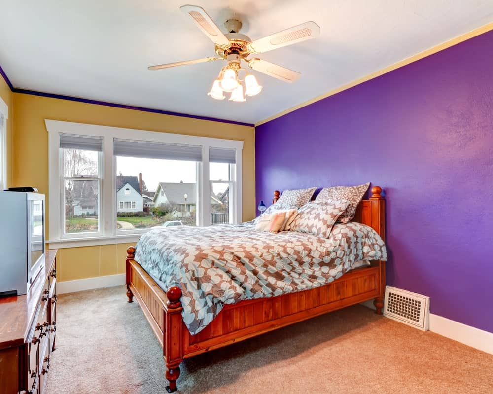 A focused shot at this primary bedroom's large bed with a wooden frame surrounded by yellow and purple walls. The room also features carpet flooring.