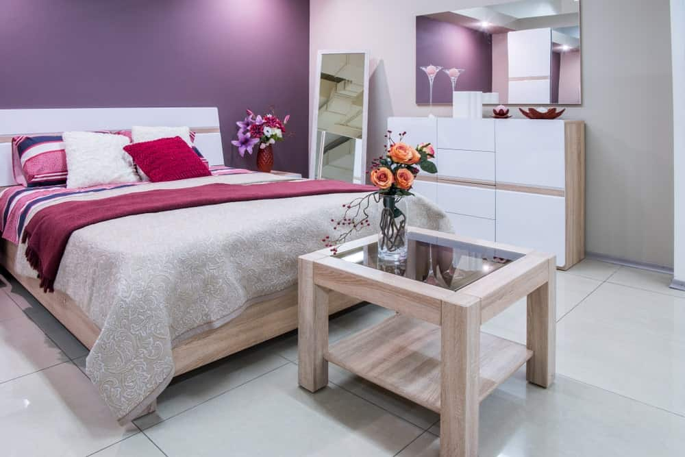 A primary bedroom featuring medium tiles flooring and a purple wall, along with a comfy bed.