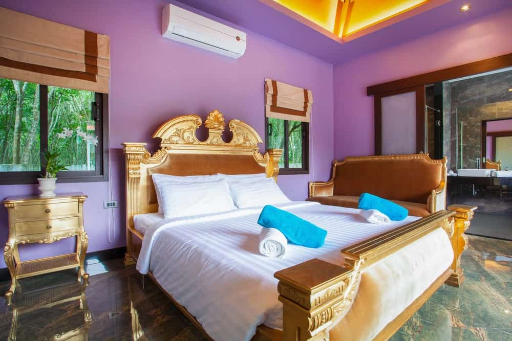 This primary bedroom boasts a luxurious bed setup along with other elegant-looking furniture. The room's flooring is stunning, together with its ceiling. The room also has its own large bathroom.