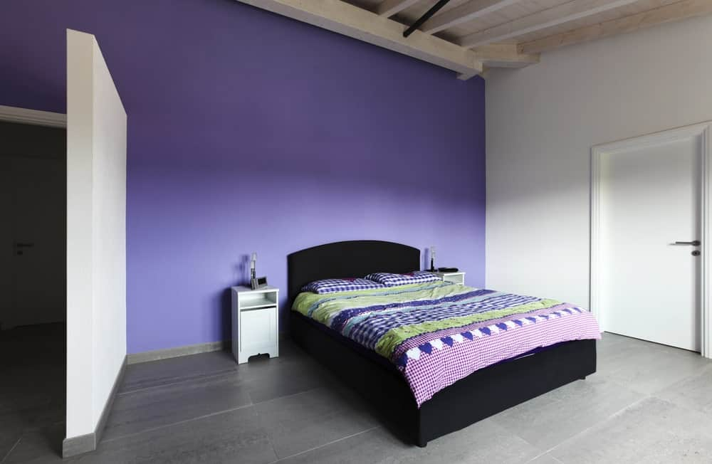 Minimalist primary bedroom with hardwood floors, white and purple walls and a wooden ceiling with beams. The room has a modish bed setup with bedside tables on both sides.