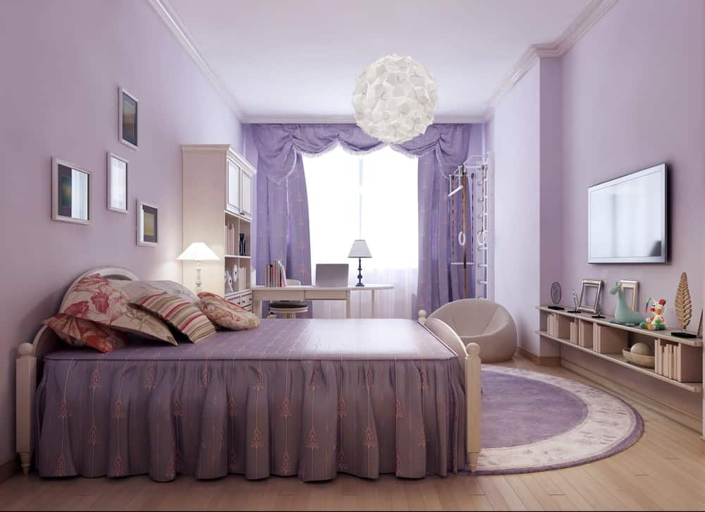 Primary bedroom featuring a gorgeous and cozy purple bed and a study desk on the side, surrounded by purple walls and purple window curtains. The room is lighted by a charming pendant light.