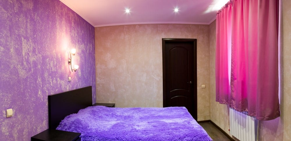 A bright primary bedroom with pink and beige walls with lovely designs. The room is lighted by recessed and wall lights.
