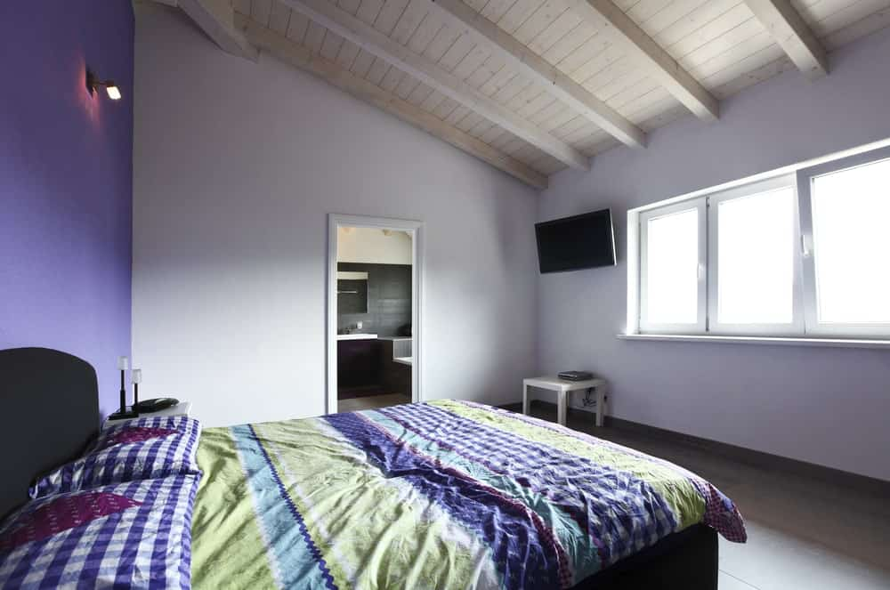 A simplistic primary bedroom with a large comfy bed and a widescreen TV on the side. The room also offers its own bathroom.