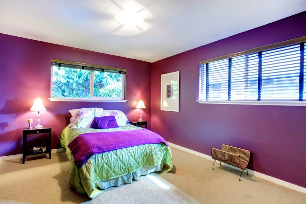 A spacious primary bedroom featuring purple walls and carpet floors. The bed is lighted by charming table lamps on both sides.