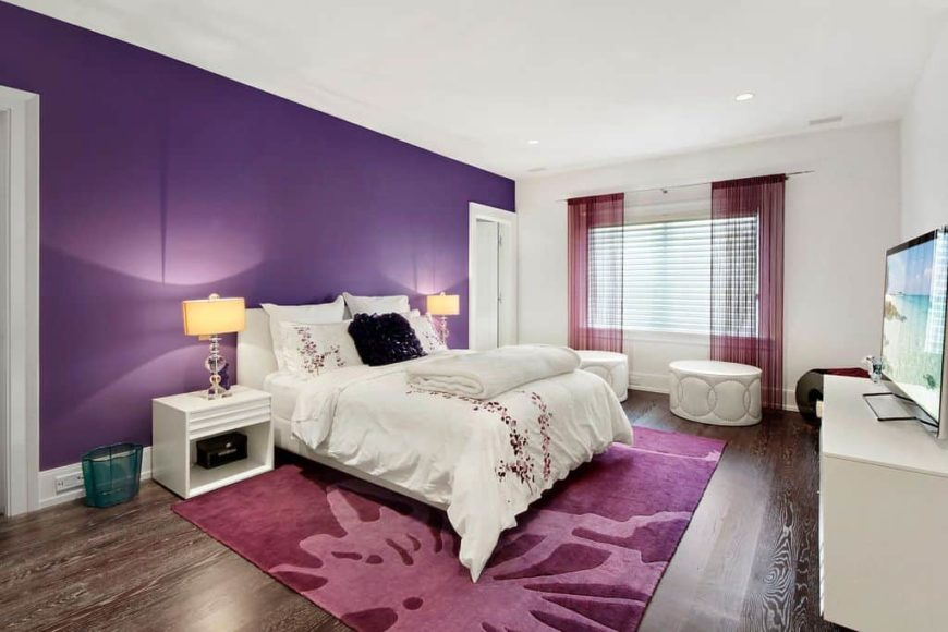 A spacious primary bedroom featuring hardwood floors, a purple wall and a white ceiling. The room has a nice white bed setup lighted by classy table lamps, along with a flat-screen TV in front.