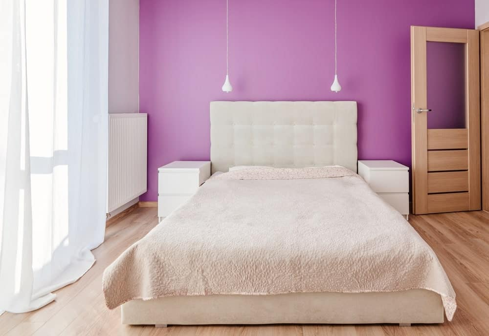 A focused look at this primary bedroom's white bed setup lighted by two table lamps. The room has a purple wall and charming white window curtains.