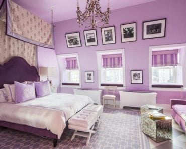 A purple master bedroom boasting a gorgeous purple bed and a purple couch, along with three windows both with purple window curtains. The room is lighted by a fancy chandelier.